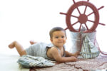 Precioso niño vestido de marinero con un timón.